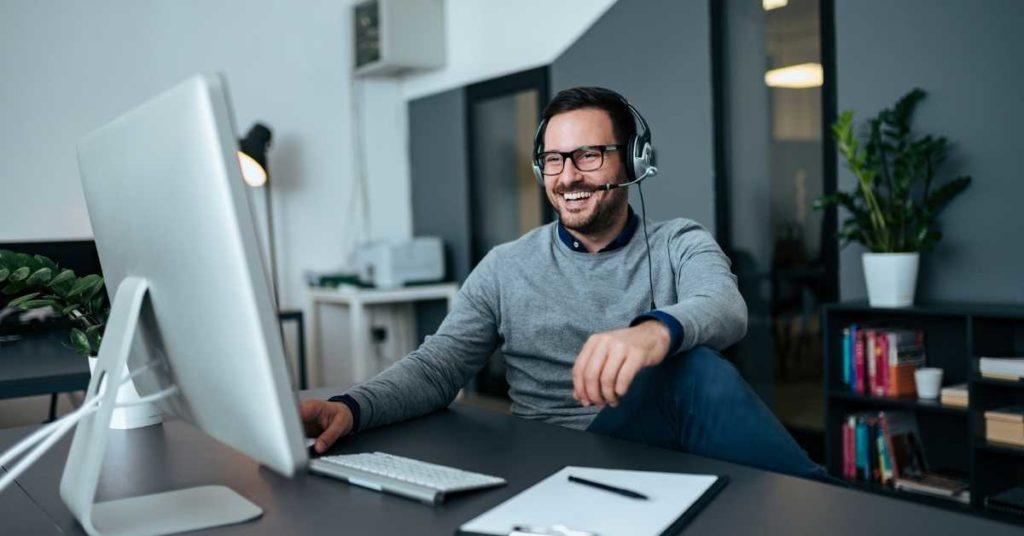 Wie funktionieren Zoom Meetings? mann glücklich vor dem computer